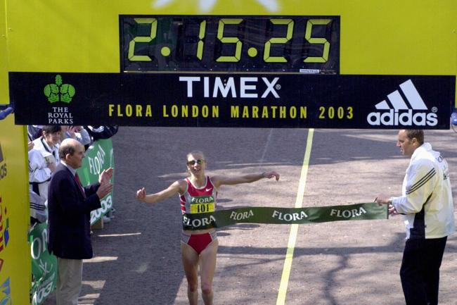 Paula Radcliffe crosses the line to set a new marathon world record