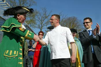 Town crier Dick Smith shakes hands with Alain Roux at the Beaconsfield cheese-makers market