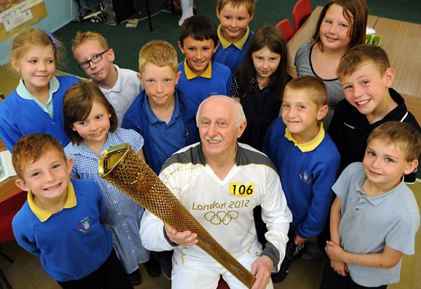 Stan Wild shows the Olympic torch he carried in the relay through York to youngsters at Tang Hall school