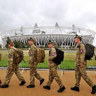 A group of soldiers march in front of the Olympic Stadium as they make their way to a security checkpoint at the Olympic Park entrances