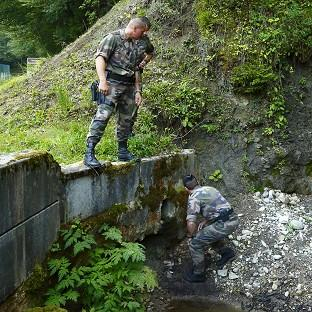 Ealing Times: French police inspect a drain under the road to the murder scene at Cheverlaine near Annecy