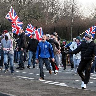Loyalists react after being attacked by nationalists throwing stones from the nationalist Short Strand area of Belfast