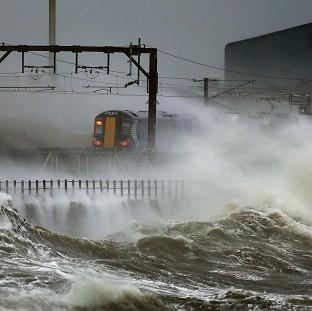 A train is lashed by waves along the coast at Saltcoats as Scotland has been warned to expect a storm surge.