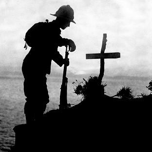 A British soldier pays his respects at the grave of a colleague after the Gallipoli landings in 1915