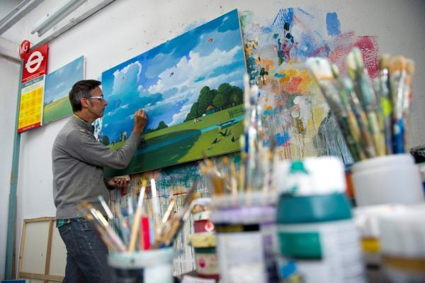 Artist at work: Martin Grover in his studio. Note his famous Driver's Prayer bus stop on the left