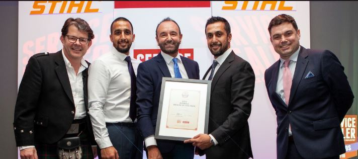 Amar and Rajiv Parmar receive the Garden Machinery Dealer of the Year Award from Ken Brewster, UKsales and marketing director from sponsor Husqvarna, with Service Dealer owner Duncan Murray?Clarke, left andcomedian Charlie Baker, right