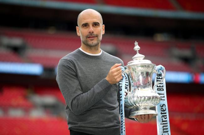 Manchester City manager Pep Guardiola lifts the FA Cup
